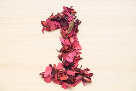numeral: Number 1 (one), arabic numeral made from dried red flower on wood background