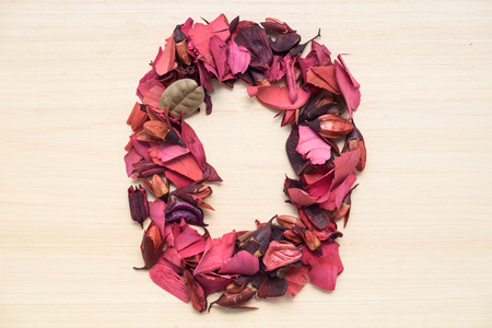arabic number: Number 0 (zero), arabic numeral made from dried red flower on wood background