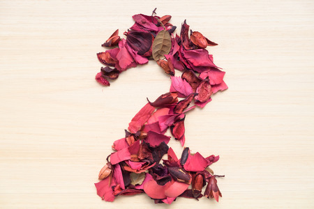 arabic number: Number 2 (two), arabic numeral made from dried red flower on wood background