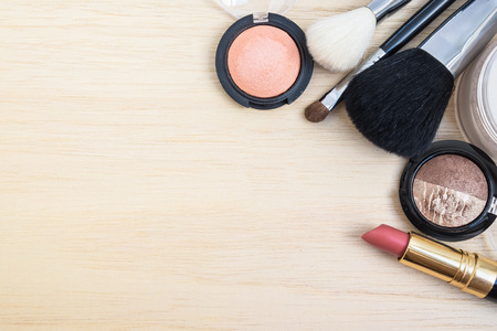 Woman earth tone cosmetics  (make-up) - eyeshadow, brush on, lipstick, powder, brush. Top view with space for text.