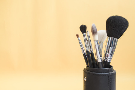 make up brushes: Selective focus on different kind of women make up brushes on light yellow background