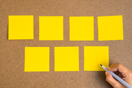 Seven blank yellow sticky notes on brown wood board with human hand hold a pen Stok Fotoğraf