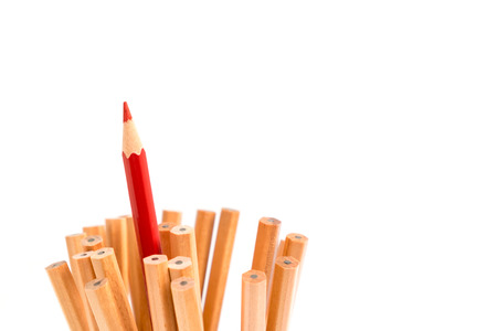 divergence: Red colored pencil stand out of other brown pencils - business concept of leader and success - isolated object on white background