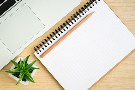 spiral notebook: Top view of office desk table with open spiral notebook, pencil, small tree, and laptop on wood table Stock Photo