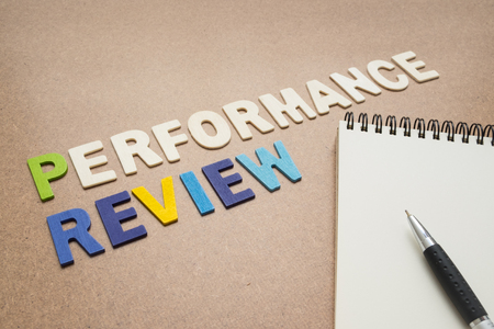pen quality: Performance review text with open spiral notebook and pen on brown background - concept of quality measurement Stock Photo