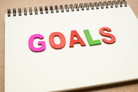 uppercase: Text GOALS wording on open spiral notebook - colorful GOALS uppercase letter on open notebook