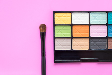 eyeshadow: Colorful eyeshadow palette with eye make up brush - colorful cosmetics on bright pink background Stock Photo