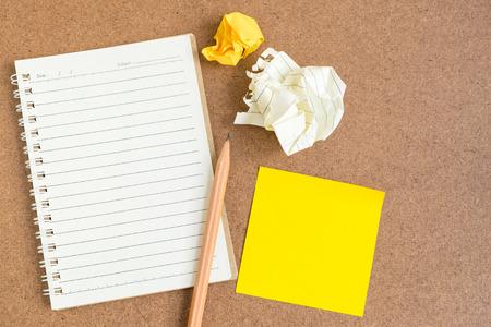 lapiz y papel: Vista superior de la libreta de espiral abierta, línea papel vacía con el lápiz de color marrón y amarillo notas adhesivas y la bola de papel arrugado - papel de cuaderno sobre fondo marrón Foto de archivo