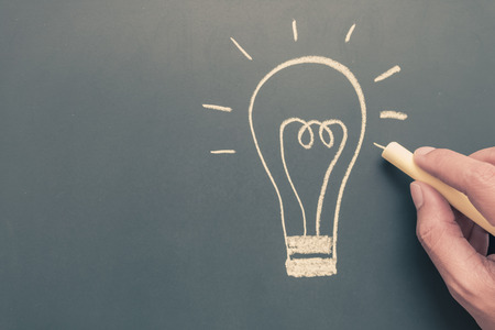 Hand writing light bulb on blackboard background with human hand hold chalk - business concept idea with space - vintage filter