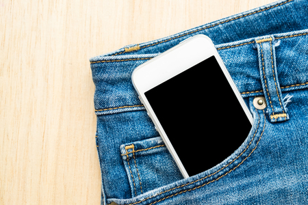 denim trousers: Mobile phone in blue jeans denim trousers front bag on wooden background