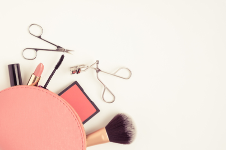 Top view of pink cosmetic bag consist of makeup brush, lipstick, brush on, scissors, mascara,  eyelash curler on white background - vintage filter tone Stok Fotoğraf