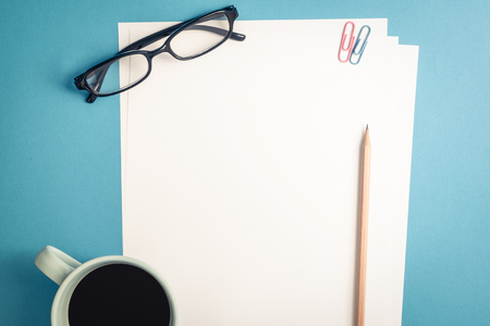 pencil and paper: Desk above, top view of an empty white plain paper with brown pencil, paper clips, black glasses and a glass of coffee on pastel blue background