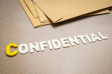 to conceal: Confidential wording on brown background with pile of brown envelope in the background