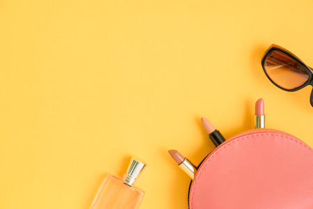 Top view of pink cosmetic bag consist of three lipsticks, fashion sunglasses, and perfume on pastel light yellow background