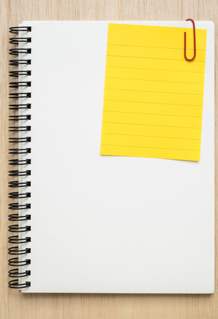 note notebook: Yellow line memo note clipped on white open spiral notebook on wooden background