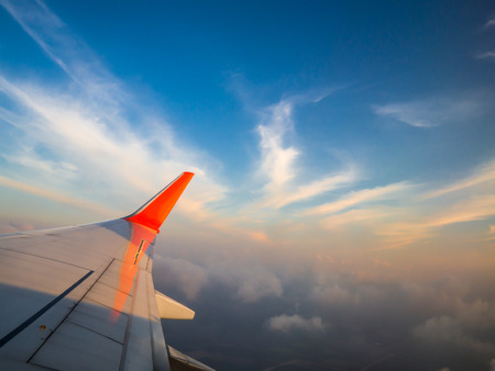 Aircraft wing - airplane fly over the cloud and blue sky in the evening Stock Photo