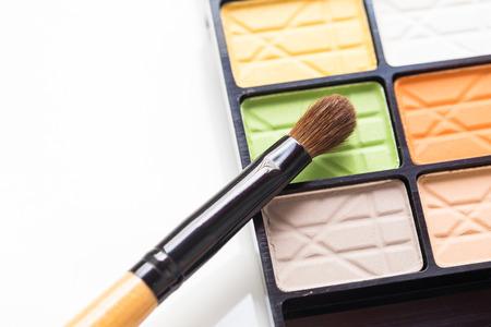 eyeshadow: Close up eye make up brush on colorful eyeshadow palette on white background Stock Photo