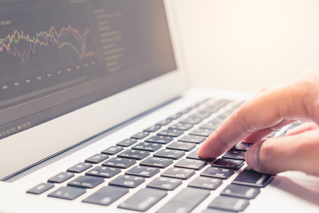 end user: Selective focus on woman hand typing on laptop keyboard with graph on screen in vintage filter tone with warm light effect - business concept of working