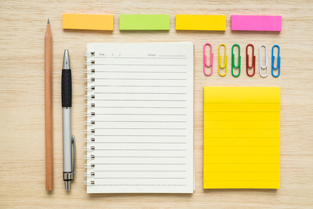 pencil and paper: Colorful set of stationery, notepad, paper clips, sticky notes, pen, pencil on wooden background - concept of back to school