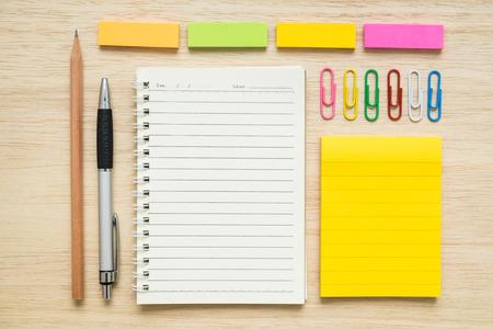 lapiz y papel: colorido conjunto de artículos de papelería, bloc de notas, clips de papel, notas adhesivas, pluma, lápiz sobre fondo de madera - concepto de regreso a la escuela Foto de archivo
