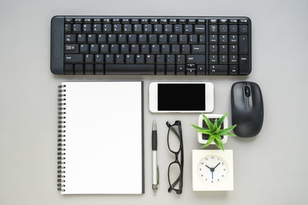 phone the clock: Top view of office desk -  wireless keyboard and mouse, notebook, mobile phone, clock, eyeglasses, pen and plant Stock Photo