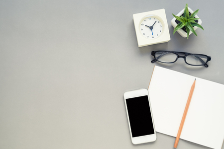 phone the clock: Desk above, table top view of office desk with notebook, pencil, mobile phone, clock, eyeglasses, plant on grey background Stock Photo