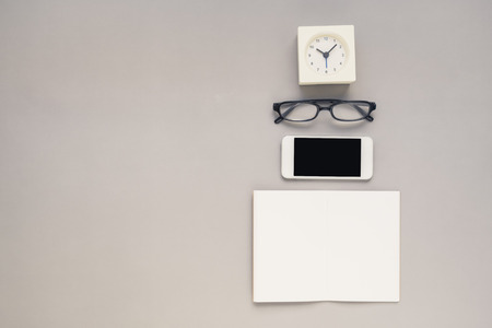 phone the clock: Desk above, table top view of office desk with notebook, mobile phone, clock, eyeglasses on grey background