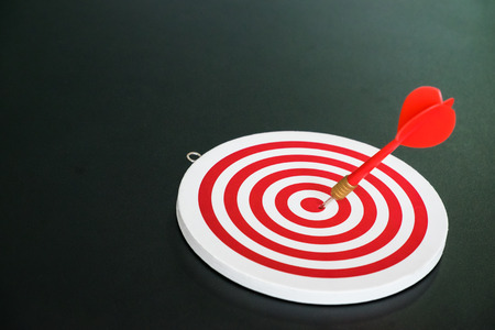Red bullseye dart with red arrow hit center of dartboard - business concept of success and goal achievement