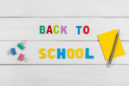 Top view of back to school wording on white wooden background with paper clips and note