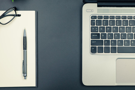 Table top view of laptop and empty notebook with pen and eyeglasses in vintage tone