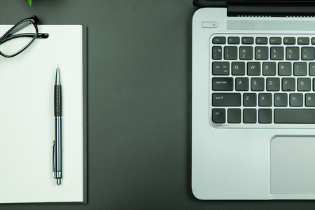 Table top view of laptop and empty notebook with pen and eyeglasses in black color Stok Fotoğraf