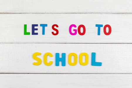 Top view of Lets go to school wording on white wooden background