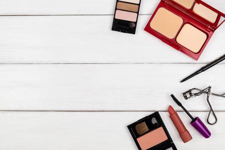 Top view of cosmetic - eye shadow, powder, blush on, lipstick - on white wooden background Stok Fotoğraf