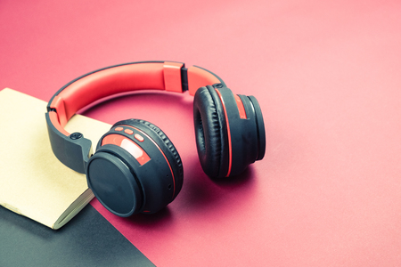 Selective focus on headphone and notebook on red and black background in vintage tone Stok Fotoğraf