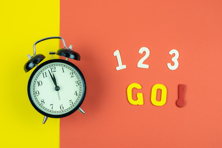 Top view of 1 2 3 Go wording with classic vintage alarm clock on colorful red and yellow background