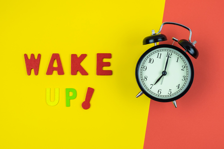 Top view of Wake Up wording with classic vintage alarm clock on colorful red and yellow background