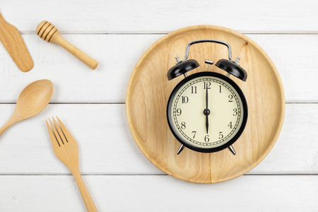 Top view of classic vintage alarm clock on wood plate with spoon and fork - concept of time for breakfast Stok Fotoğraf