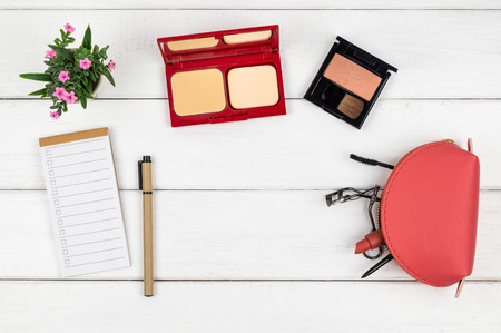 Top view of cosmetics  notebook and pen on white wood background