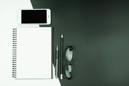 Top view of empty open notebook with smart phone and stationery on black and white background Stok Fotoğraf