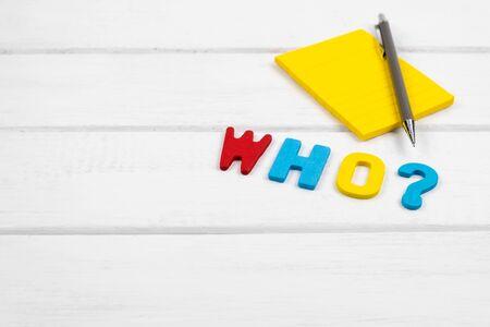 Wer formuliert auf weißem Holzhintergrund - Konzept von 5 Ws-Wh-Fragen