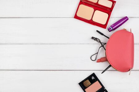 Top view of cosmetic items and pink bag on white wood background