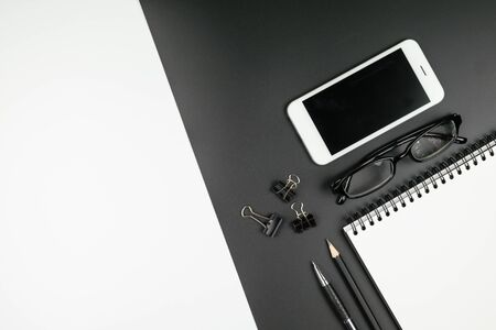 Top view of minimal office desk with notebook, pen, pencil, mobile phone