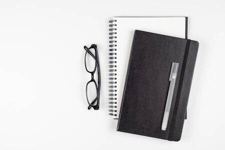 Top view of minimal office desk with notebooks pen and eyeglasses Stok Fotoğraf