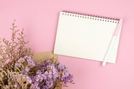 Top view of empty notebook and violet statice and white caspia flower bouquet on pastel pink background