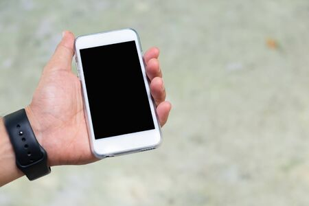 A man hold white mobile phone in his left hand