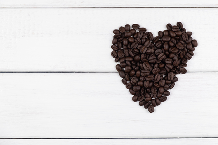 Top view of coffee beans in heart shape on white wooden background Stok Fotoğraf