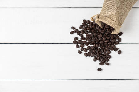Top view of coffee beans in a bag on white wooden background Stok Fotoğraf