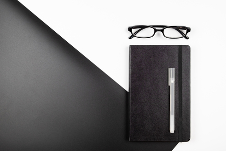 Top view of minimal office desk with notebook pen and eyeglasses