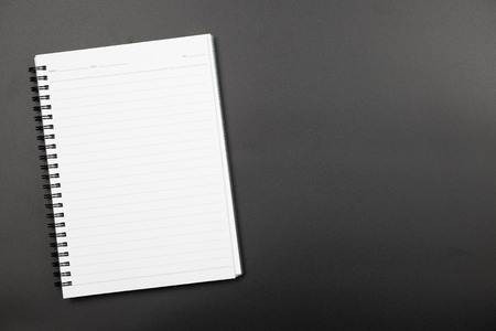 Top view of spiral empty line notebook on black background
