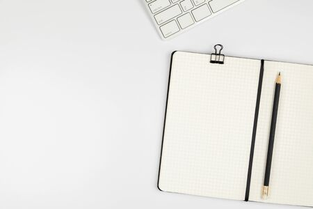 Top view of minimal office desk with empty grid notebook pencil on white table background